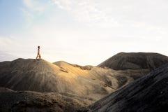 Le jeune homme entrent vers le haut dans le désert de sable photos stock
