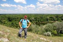 Le jeune homme a escaladé une colline au-dessus de la rivière Photo stock