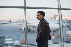 Le jeune homme est fenêtre proche debout à l'aéroport et à l'avion de observation avant le départ Foyer sur le sien de retour Images libres de droits