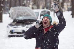 Le jeune homme est sous l'effort parce que sa voiture décomposée sur la neige DA photos stock