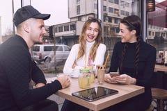 Le jeune homme et deux femmes s'asseyant dans le café font des emplettes Images stock