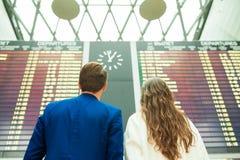 Le jeune homme et la femme dans l'aéroport international regardant l'information de vol embarquent Photos libres de droits
