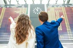 Le jeune homme et la femme dans l'aéroport international regardant l'information de vol embarquent Photographie stock