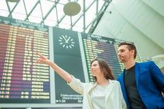 Le jeune homme et la femme dans l'aéroport international regardant l'information de vol embarquent Photo stock
