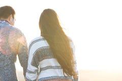 Le jeune homme et la femme embrassent dehors sur le coucher du soleil d'automne Image stock