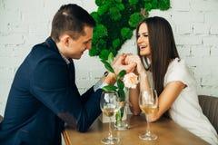 Le jeune homme et la femme gais datent dans le restaurant Ils se reposent à la table et regardent l'un l'autre avec amour Photo libre de droits