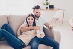 Le jeune homme et la femme regardent la TV, elle est excité de ce qui il s Photo stock