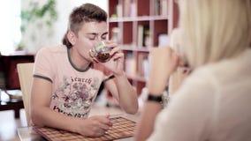 Le jeune homme et la femme s'asseyent à la table et aux boissons potables dans la cuisine banque de vidéos