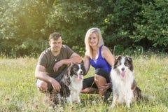 Le jeune homme et la femme s'asseyent dans l'herbe avec une paire de chiens Photo stock