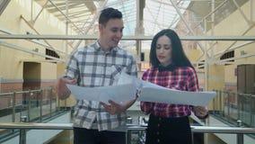 Le jeune homme et la femme se réunissent dans le hall au centre d'affaires pour discuter des documents banque de vidéos