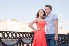 Le jeune homme et la femme se tiennent ensemble au remblai de ville regardant avec confiance en avant Photographie stock