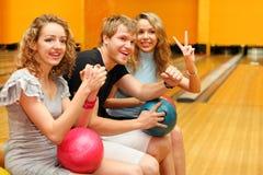 Le jeune homme et les filles s'asseyent avec des billes dans le club de bowling Photos stock