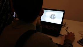 Le jeune homme examine le logiciel de PC pour modeler des satellites de l'espace sur l'ordinateur portable banque de vidéos