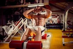 Le jeune homme faisant des exercices abdominaux de redressement assis mettent hors jeu pour enfoncer le gymnase images libres de droits