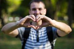 Le jeune homme fait des mains dans la forme du coeur d'amour Photographie stock libre de droits