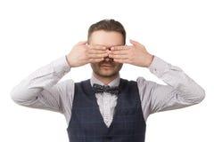 le jeune homme a fermé ses yeux avec des mains, d'isolement sur le blanc images stock
