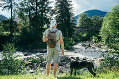 Le jeune homme fort reste la rivière proche de montagnes avec le chien et rechercher la vue Photographie stock