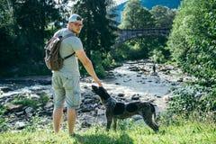 Le jeune homme fort reste la rivière proche de montagnes avec le chien et rechercher la vue Photos stock