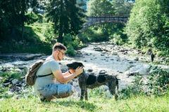Le jeune homme fort reste la rivière proche de montagnes avec le chien et rechercher la vue Photos libres de droits