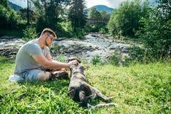 Le jeune homme fort reste la rivière proche de montagnes avec le chien et rechercher la vue Images libres de droits
