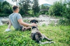 Le jeune homme fort reste la rivière proche de montagnes avec le chien et rechercher la vue Photo libre de droits