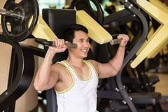 Le jeune homme fort s'exerçant pour des bras muscles à un centre de fitness W images stock