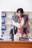 Le jeune homme fou dans la camisole de force au bureau images stock