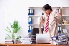 Le jeune homme fou dans la camisole de force au bureau image stock