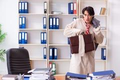 Le jeune homme fou dans la camisole de force au bureau photo libre de droits