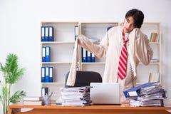 Le jeune homme fou dans la camisole de force au bureau photographie stock
