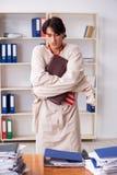 Le jeune homme fou dans la camisole de force au bureau photographie stock libre de droits