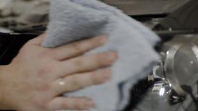 Le jeune homme frotte le phare de la voiture action Plan rapproché de la main de l'homme pour noircir le phare de chiffons de la  banque de vidéos