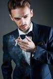 Le jeune homme fume une cigarette Photographie stock libre de droits