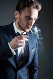 Le jeune homme fume une cigarette Image libre de droits