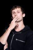 Le jeune homme fume une cigarette Photo stock