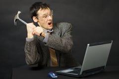 Le jeune homme furieux casse l'ordinateur de marteau Photographie stock libre de droits