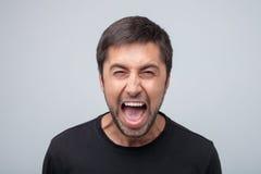 Le jeune homme furieux démontre des émotions négatives Photos stock