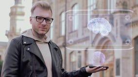Le jeune homme futé avec des verres montre un esprit humain conceptuel d'hologramme