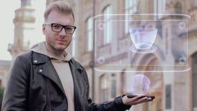 Le jeune homme futé avec des verres montre une tasse d'hologramme de café conceptuelle