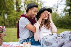 Le jeune homme gai a couvert des yeux de son amie en parc Photos stock