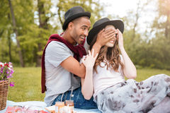 Le jeune homme gai a couvert des yeux de son amie en parc Photo libre de droits