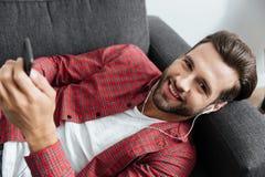 Le jeune homme gai se trouve sur le sofa causant à l'intérieur par le téléphone Photos stock