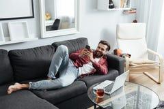 Le jeune homme gai se trouve sur le sofa causant par le téléphone Photos stock
