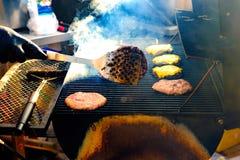 Le jeune homme grille un certain genre de viande et de légume marinés sur le gril de gaz pendant l'heure d'été photos stock