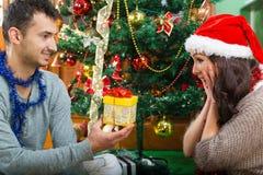 Le jeune homme heureux étonne son amie avec le cadeau de Noël Photographie stock