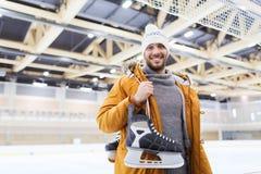 Le jeune homme heureux avec patine sur la piste de patinage Image stock