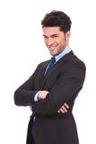 Le jeune homme heureux d'affaires avec des mains a croisé le sourire Photos stock