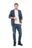 Le jeune homme heureux dans roulé vers le haut des douilles dans la chemise de denim avec des pouces lèvent le geste Photos stock