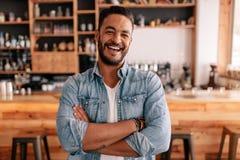 Le jeune homme heureux se tenant avec ses bras a croisé dans un café photos libres de droits