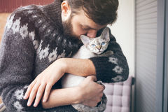 Le jeune homme heureux se tient sur un balcon avec son chat Image stock
